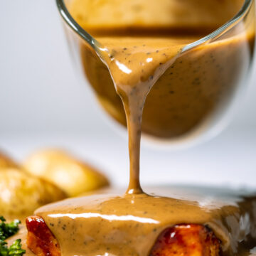 Peppercorn sauce pouring out over a tofu steak on a white plate.