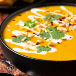 Thai butternut squash soup in a black bowl topped with crushed peanuts and fresh cilantro.