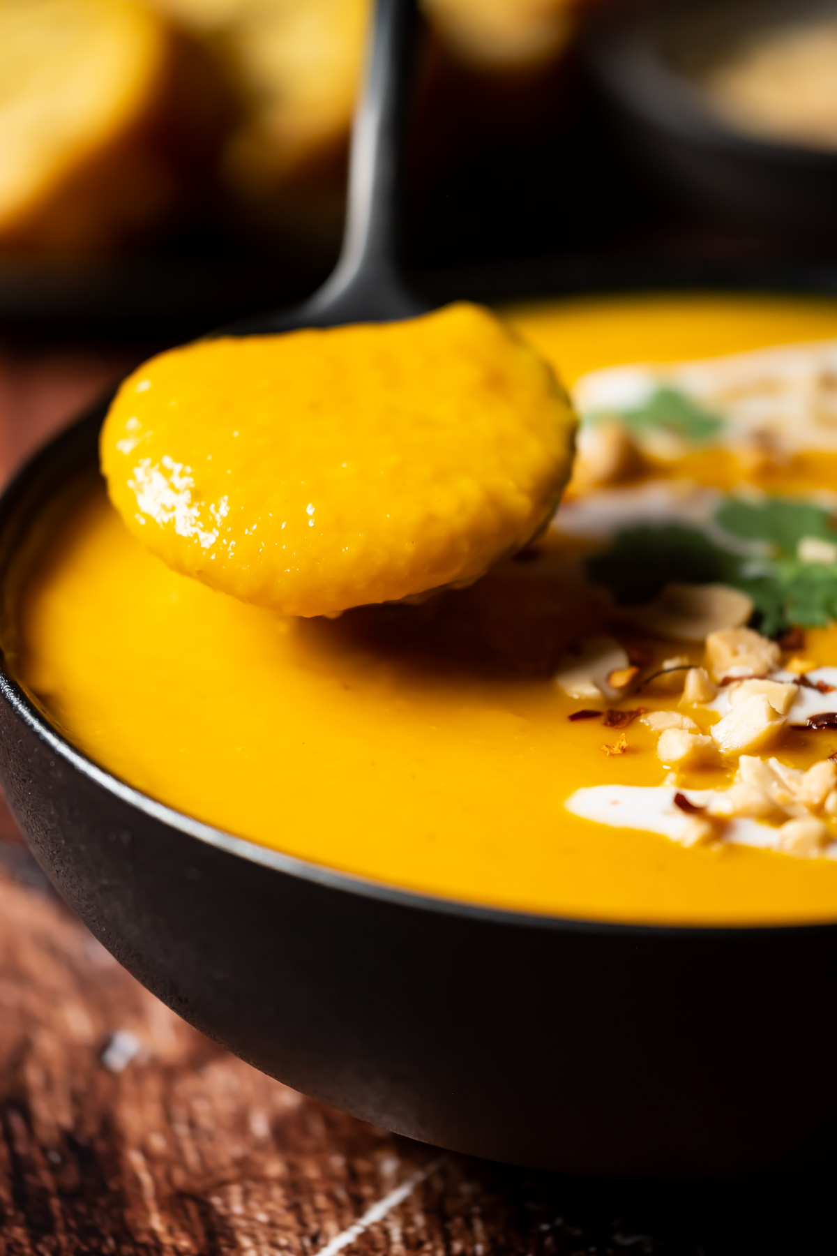 Thai butternut squash soup in a black bowl with a spoon.