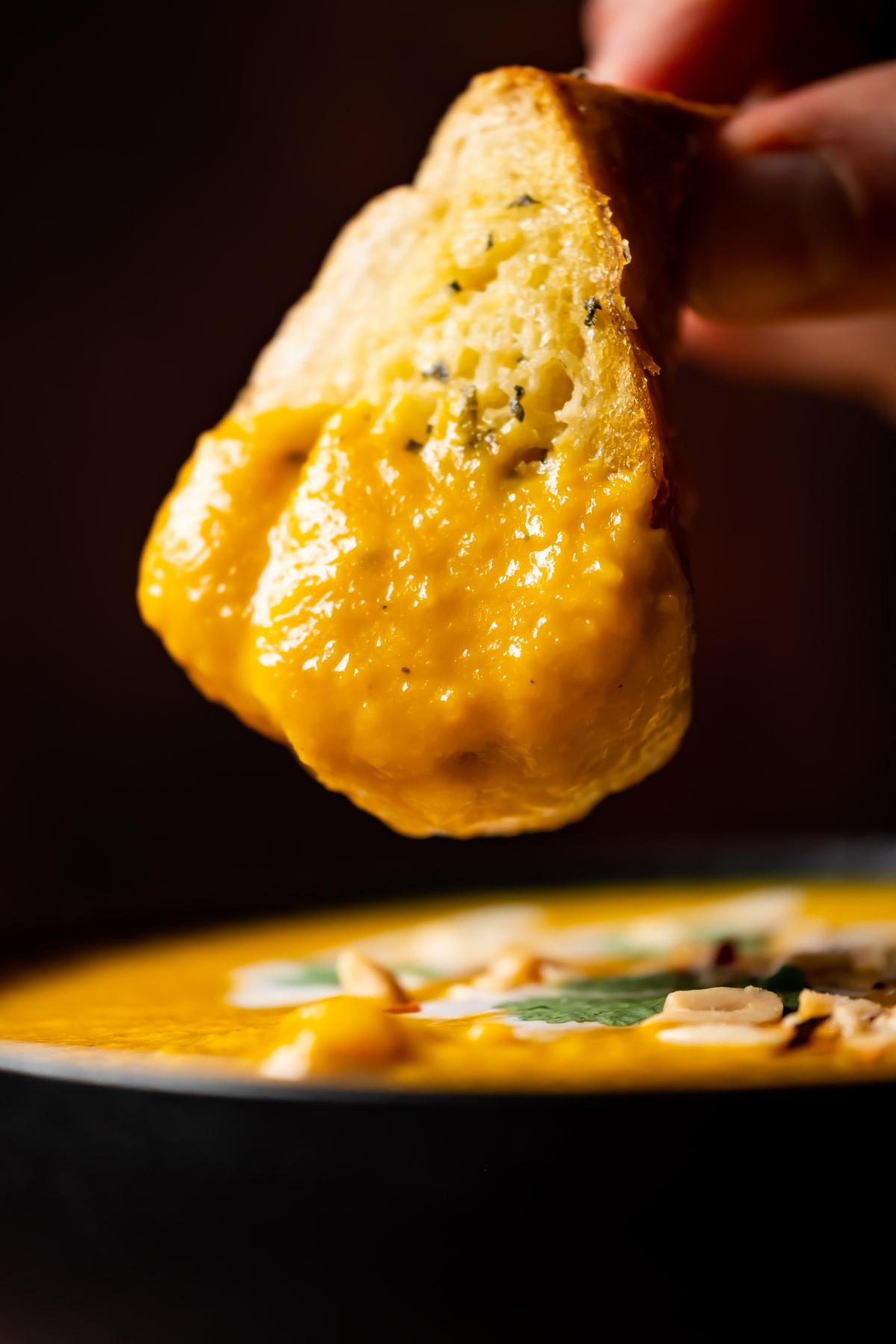 Garlic bread dipping into a bowl of Thai butternut squash soup.