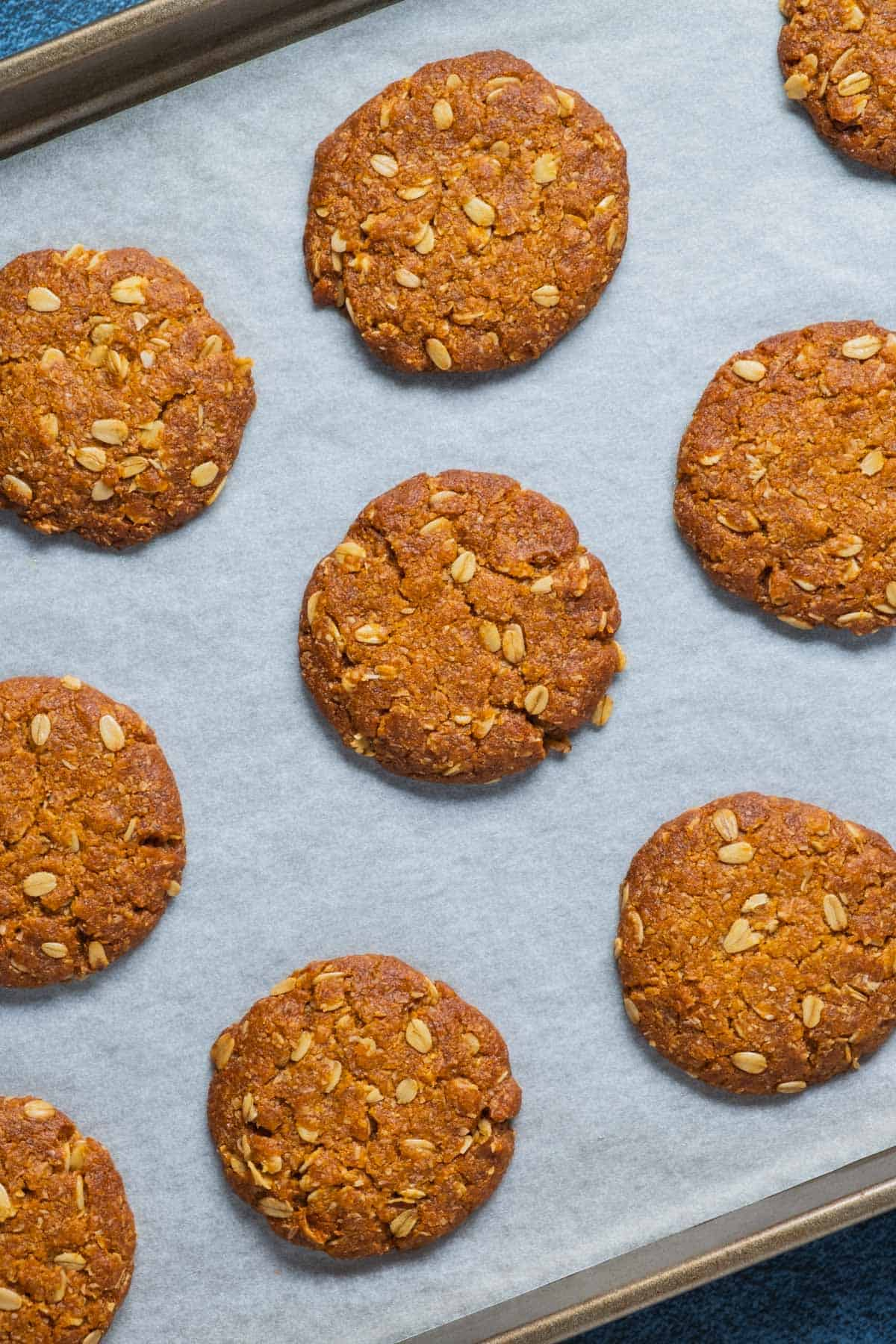 Vegan Anzac biscuits on a parchment lined baking tray.