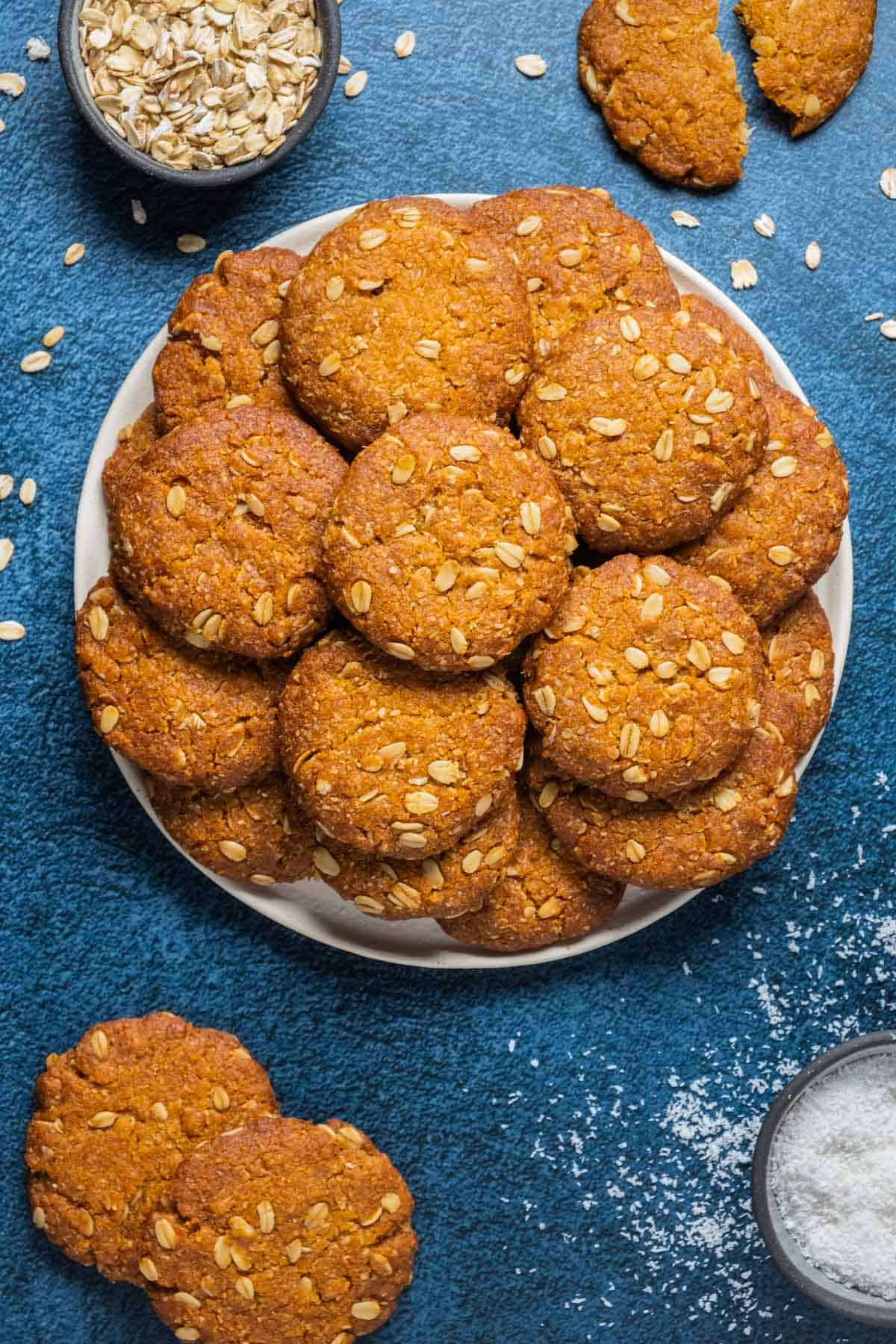 Vegan anzac biscuits stacked up on a white plate.
