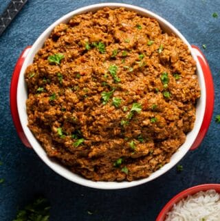 Vegan mince topped with fresh chopped parsley in a red and white dish.