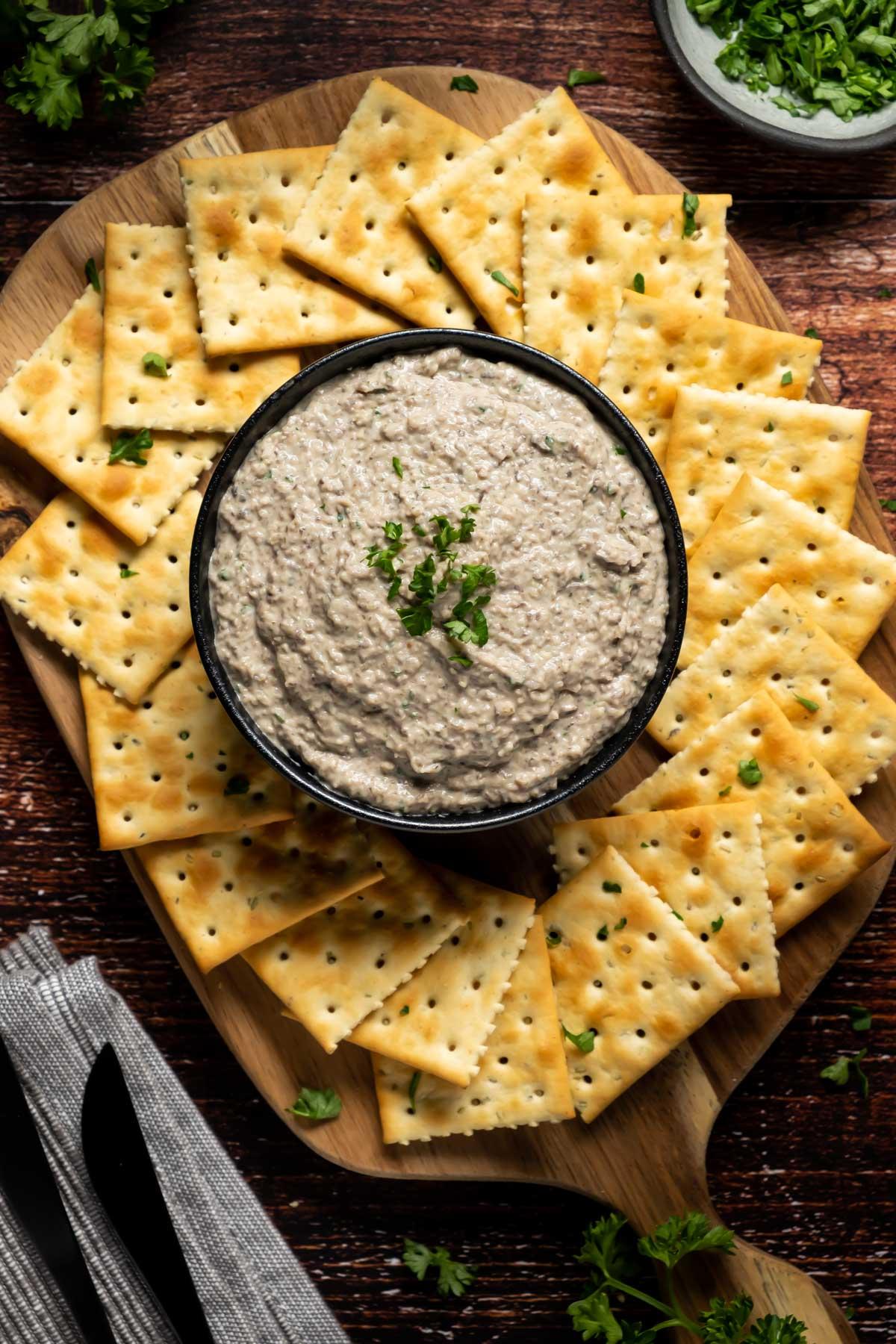 Vegan mushroom pâté in a black bowl with crackers.