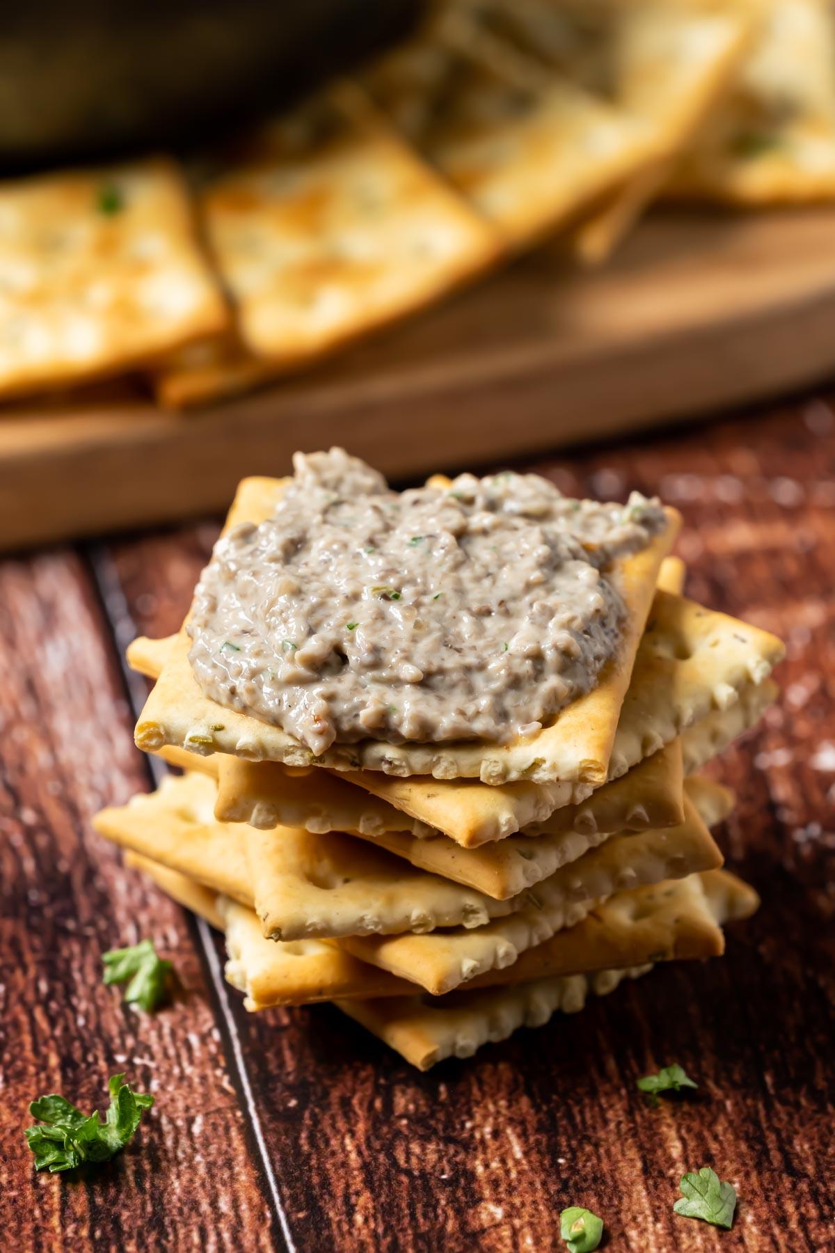 Vegan mushroom pâté on a stack of crackers.