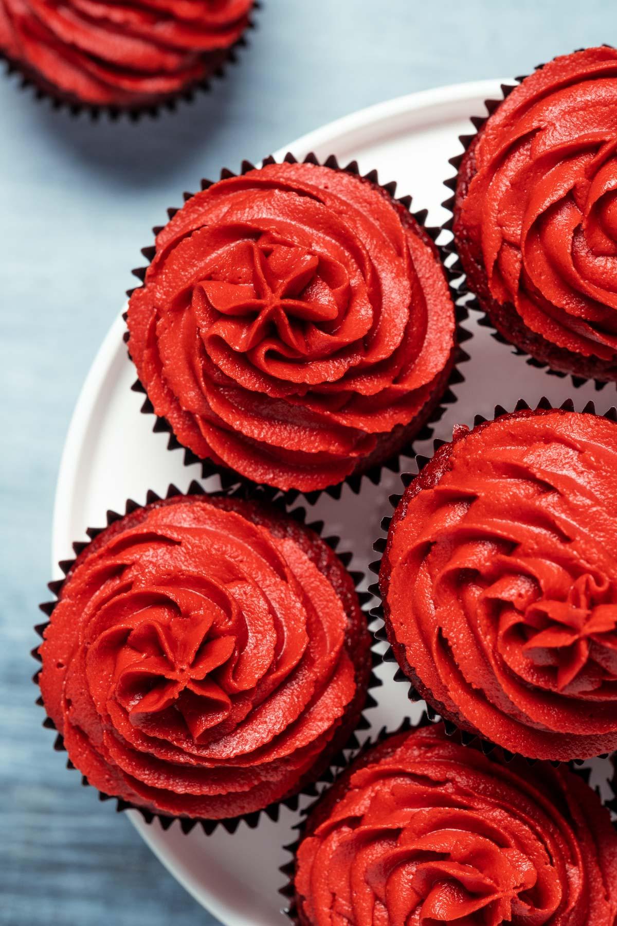 Vegan red velvet cupcakes on a white cake stand.