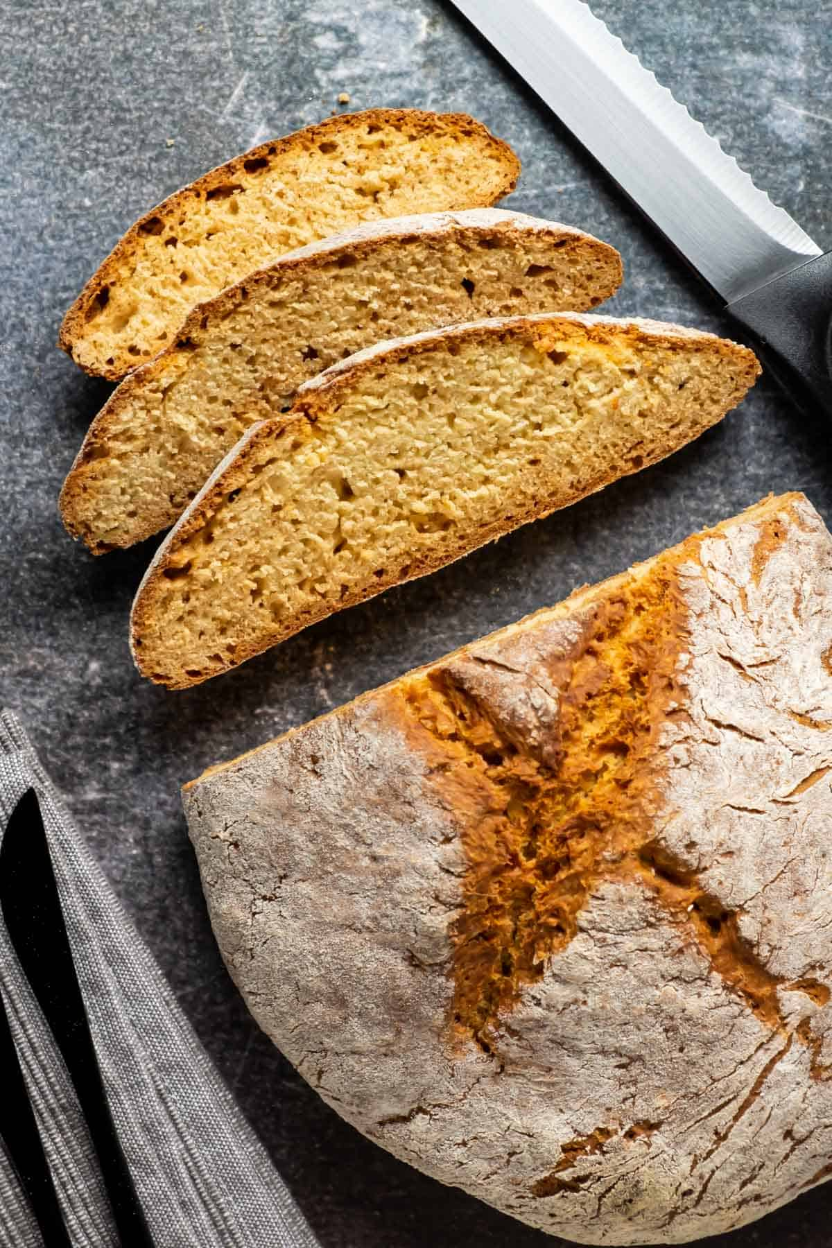 Vegan soda bread loaf with three slices cut.