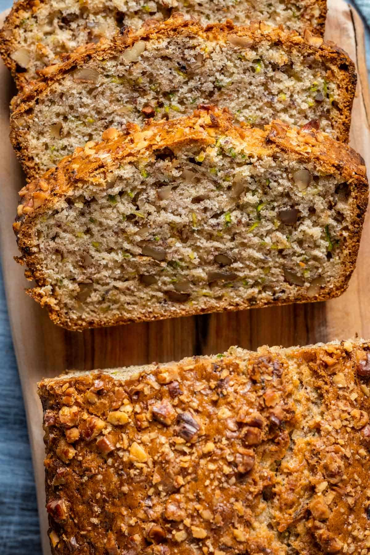 Sliced loaf of vegan zucchini bread on a wooden board.