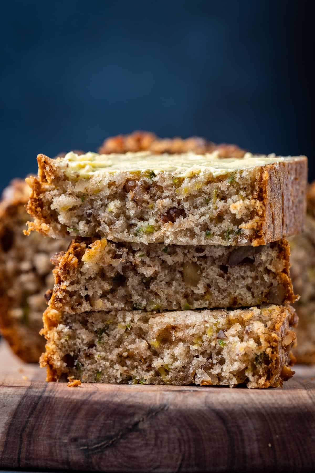 Slices of buttered vegan zucchini bread stacked up on a wooden board.
