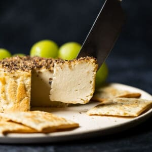 Vegan camembert cheese on a white plate with grapes and crackers.