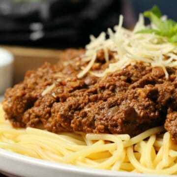 Vegan bolognese with spaghetti and vegan parmesan on a white plate.