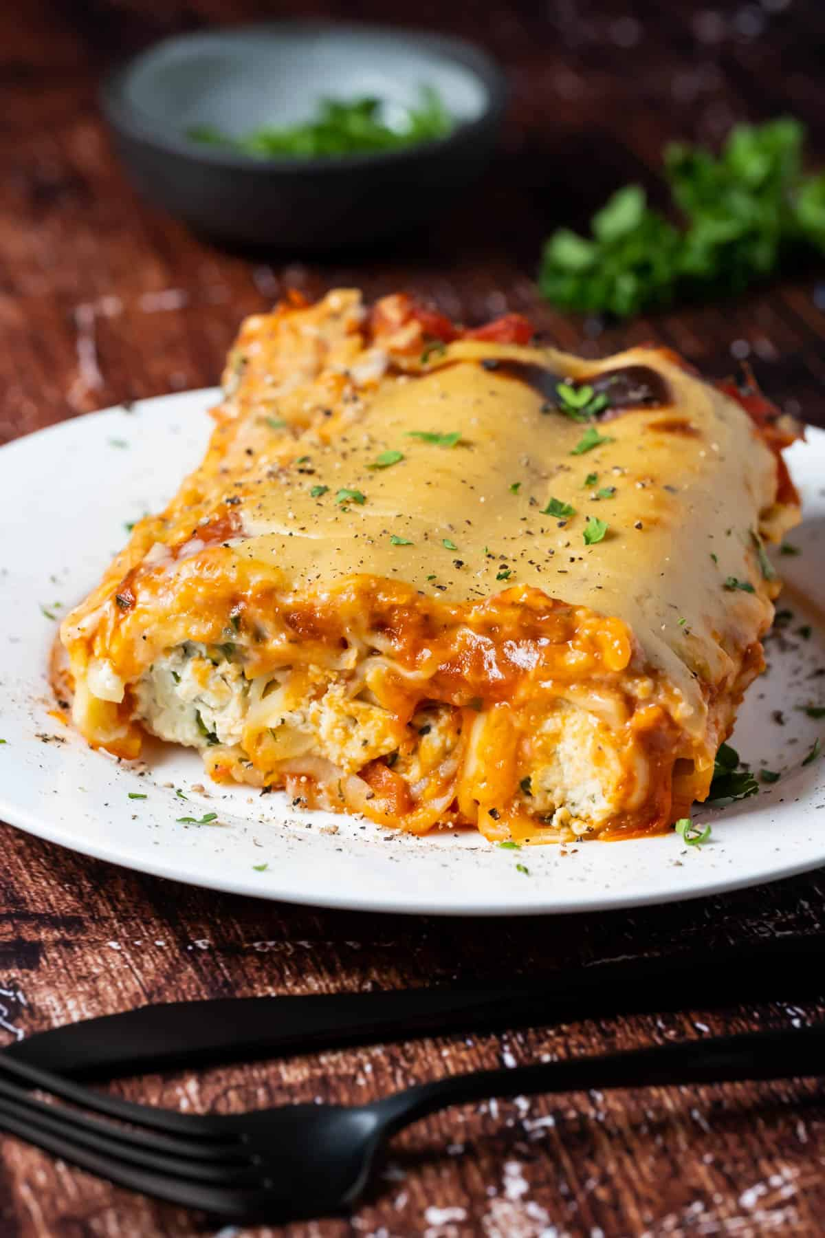 Vegan cannelloni with fresh chopped parsley on a white plate.