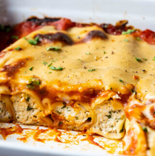 Sliced vegan cannelloni in a white baking dish.