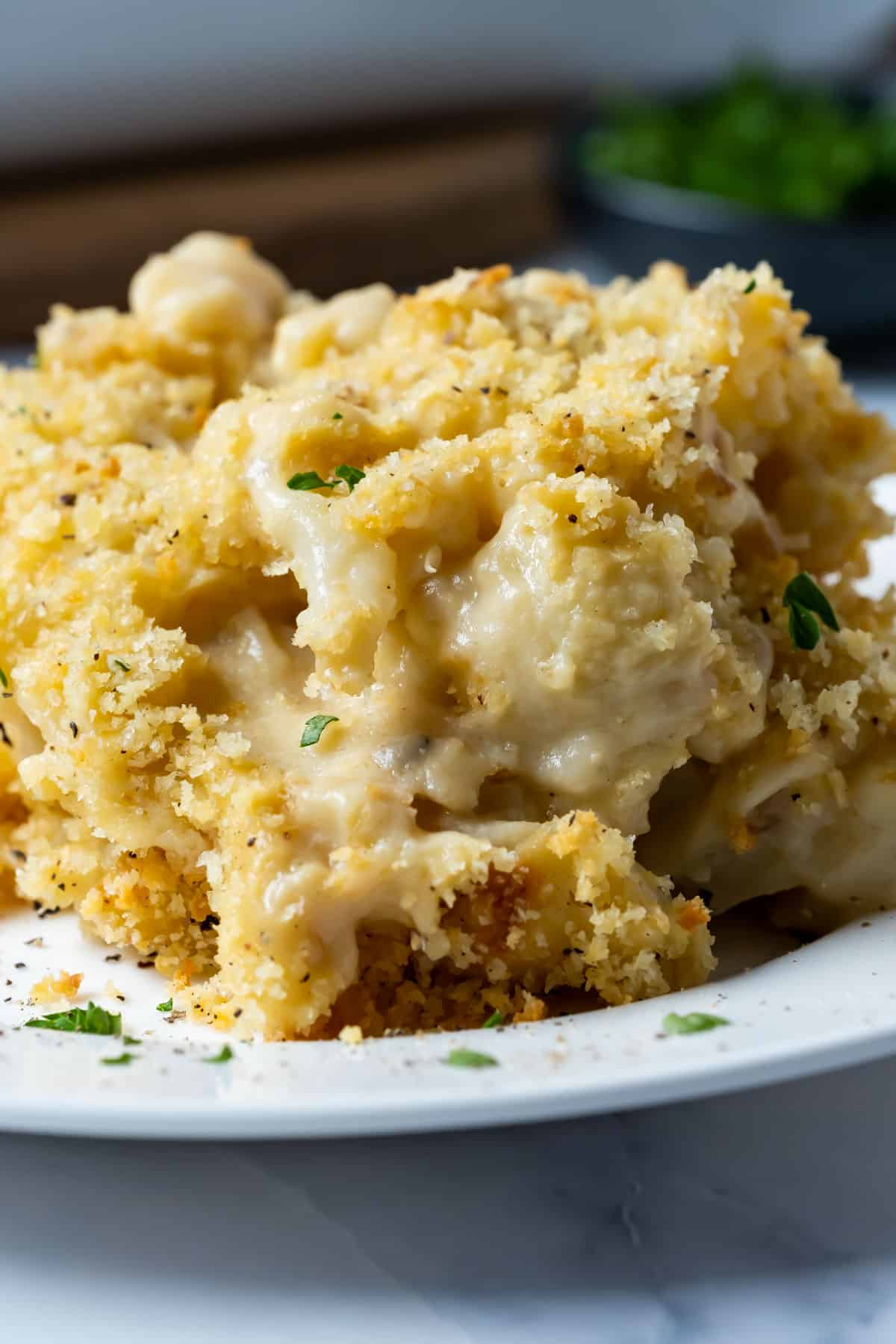 Serving of vegan cauliflower cheese on a white plate.