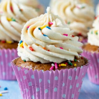 Vegan gluten free vanilla cupcakes topped with frosting and sprinkles.
