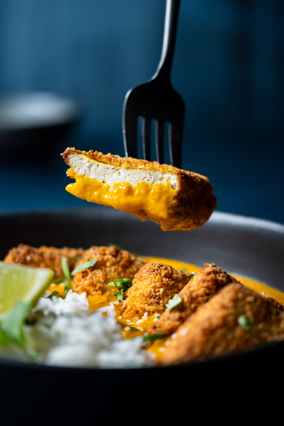 Forkful of tofu katsu curry above a bowl.