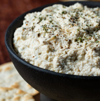 Tofu ricotta topped with ground black pepper and oregano in a black bowl.