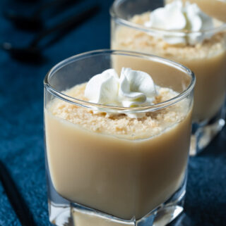 Vegan vanilla pudding topped with vegan cream and crushed cookies in small serving glasses.