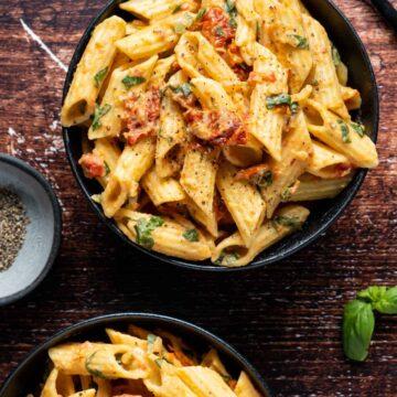Hummus pasta in black bowls.