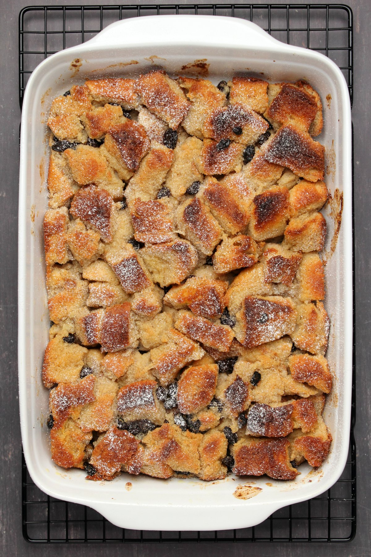 Freshly baked bread pudding topped with powdered sugar, in a white dish.