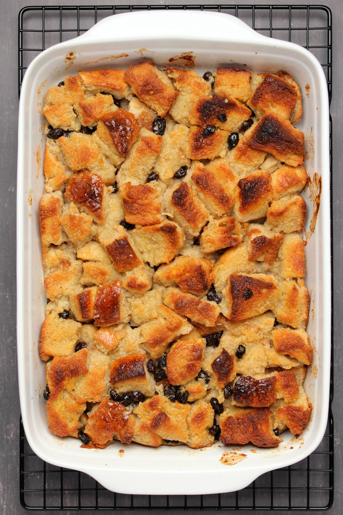 Freshly baked bread pudding in a white dish.