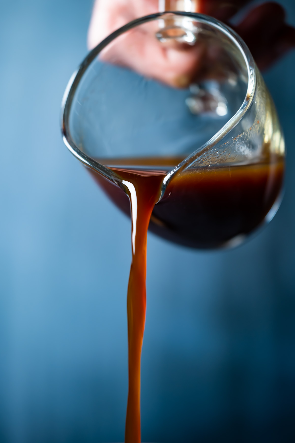 Vegan worcestershire sauce pouring from a glass jug.