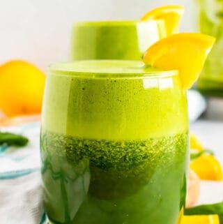 Blended green juice in glasses with orange slices.