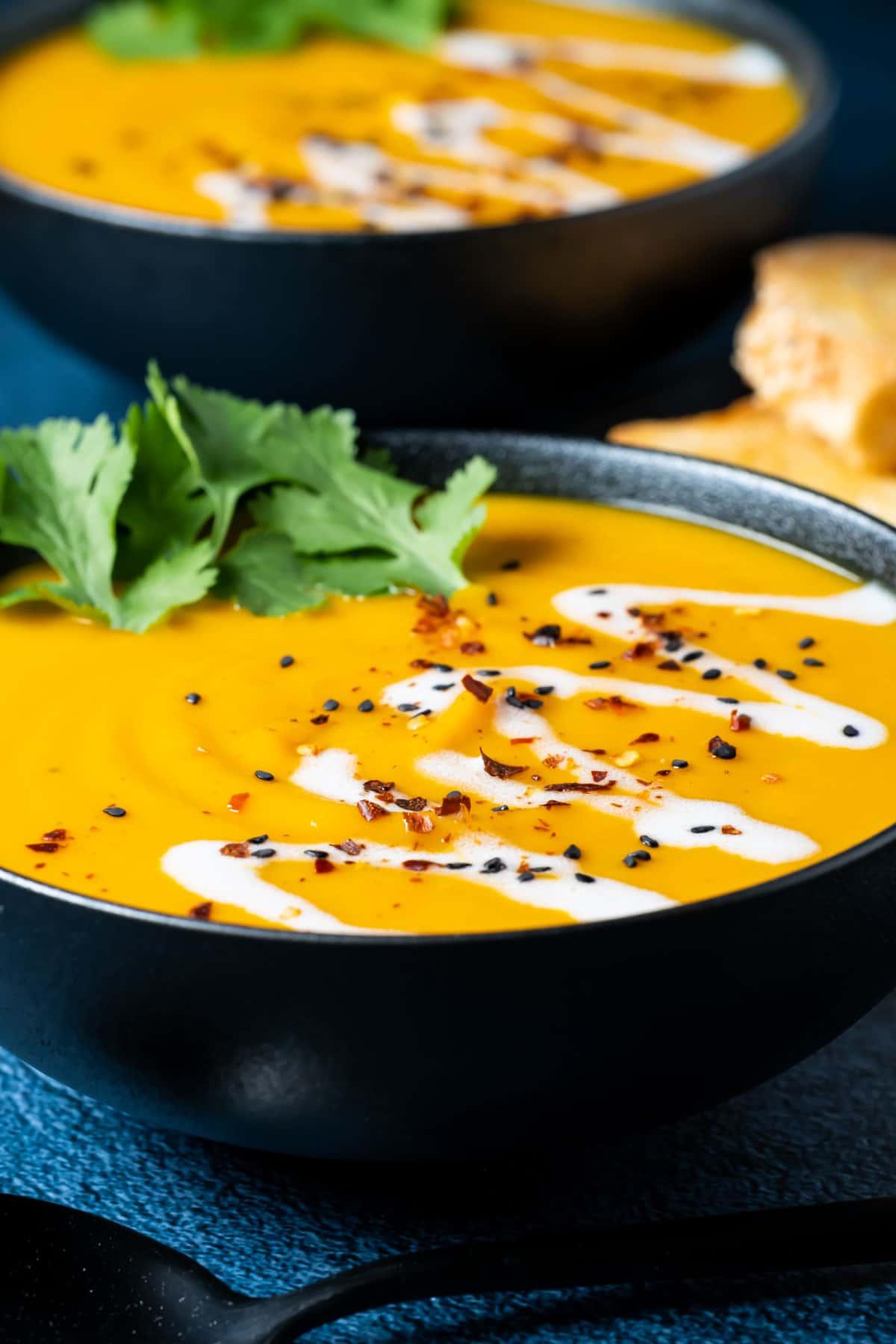 Thai sweet potato soup topped with fresh cilantro in a black bowl.
