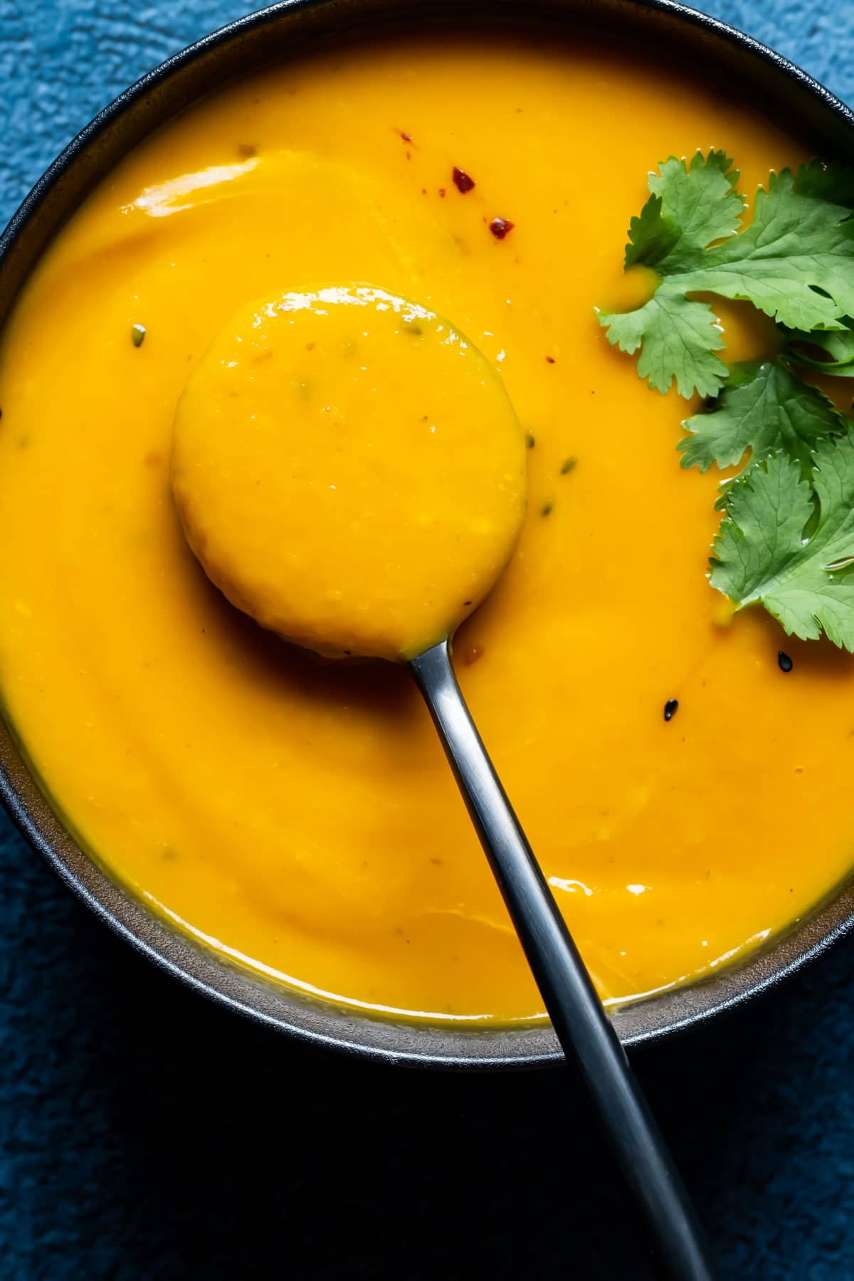 Thai sweet potato soup in a black bowl with a spoon.