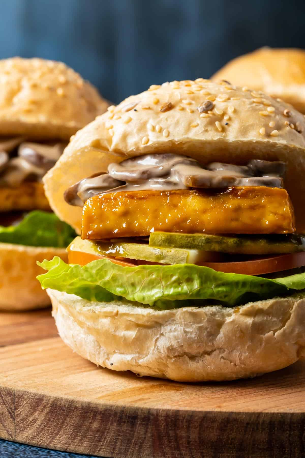 Tofu burgers on a wooden board.