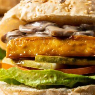 Close up photo of tofu burger topped with mushroom sauce.