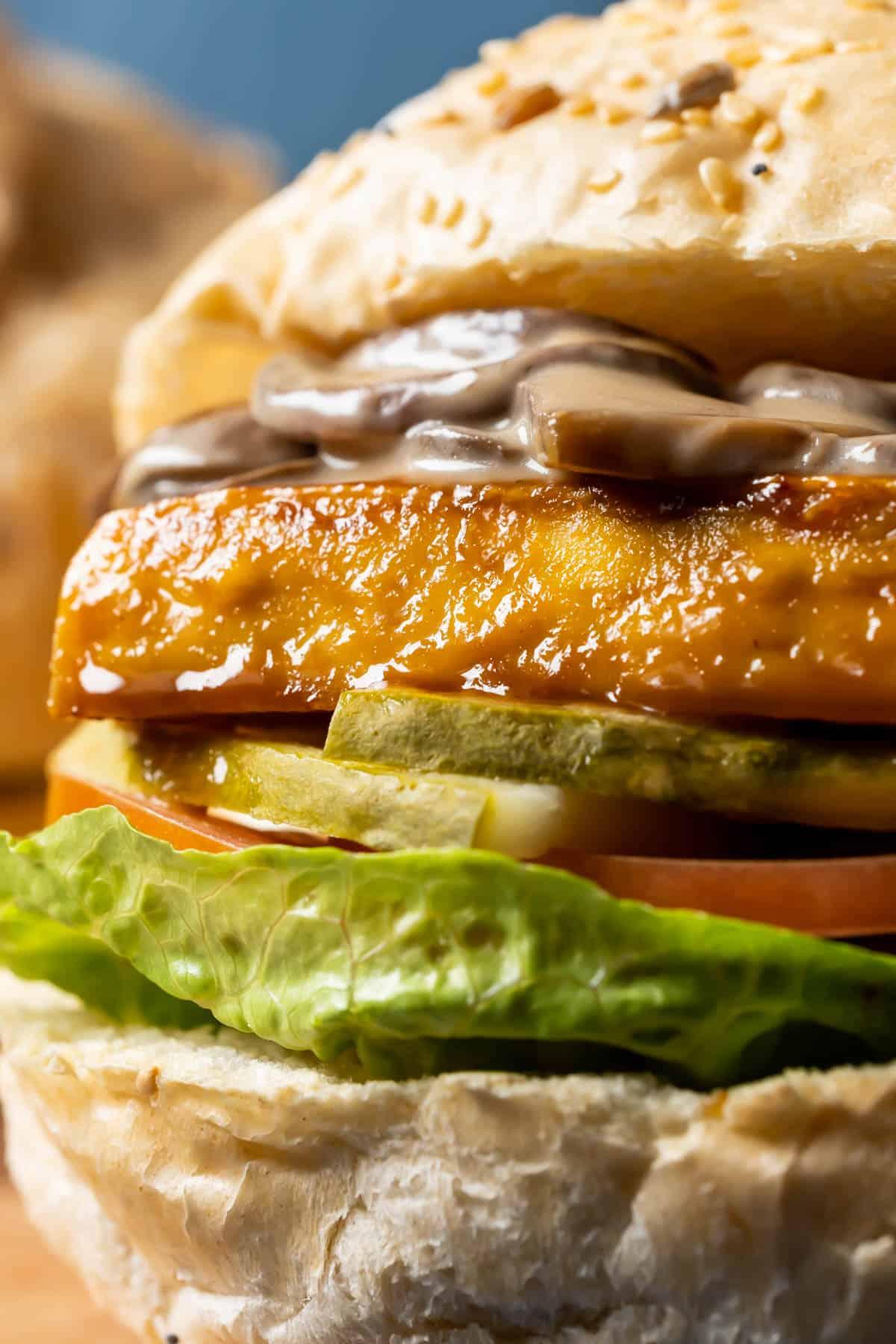 Close up photo of a tofu burger with mushroom sauce.
