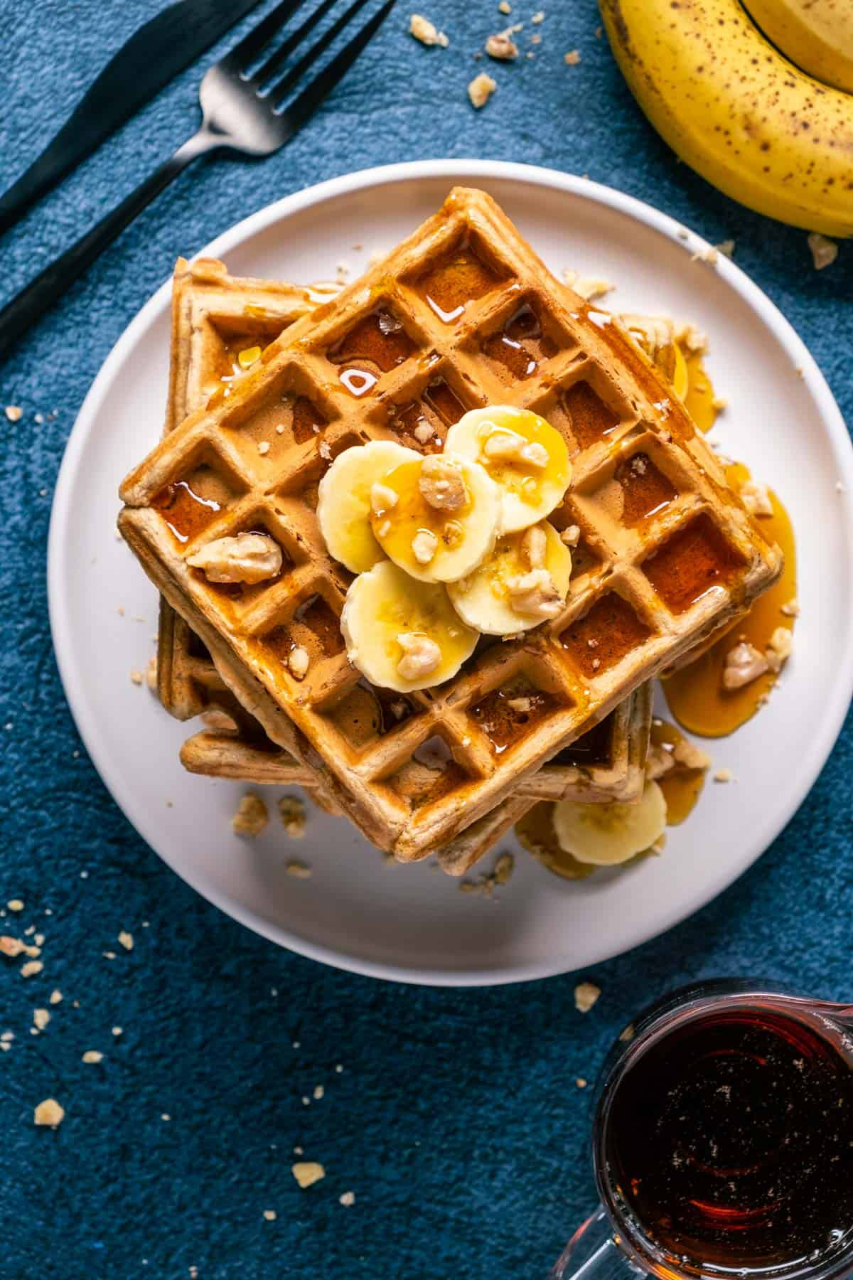 Overhead photo of a stack of vegan banana waffles topped with sliced banana, walnuts and syrup on a white plate.