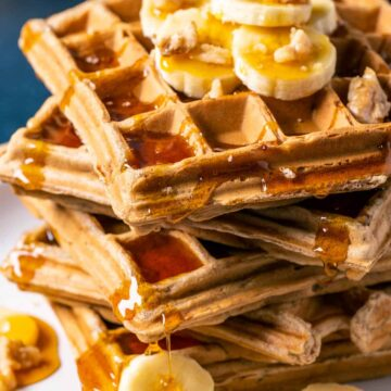 Stack of vegan banana waffles topped with sliced banana, walnuts and syrup on a white plate.