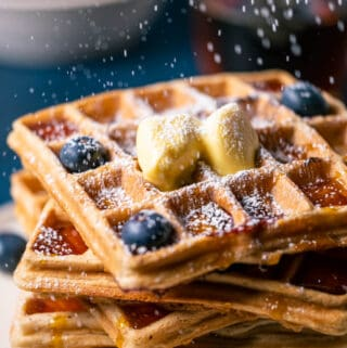 Stack of blueberry waffles on a white plate.