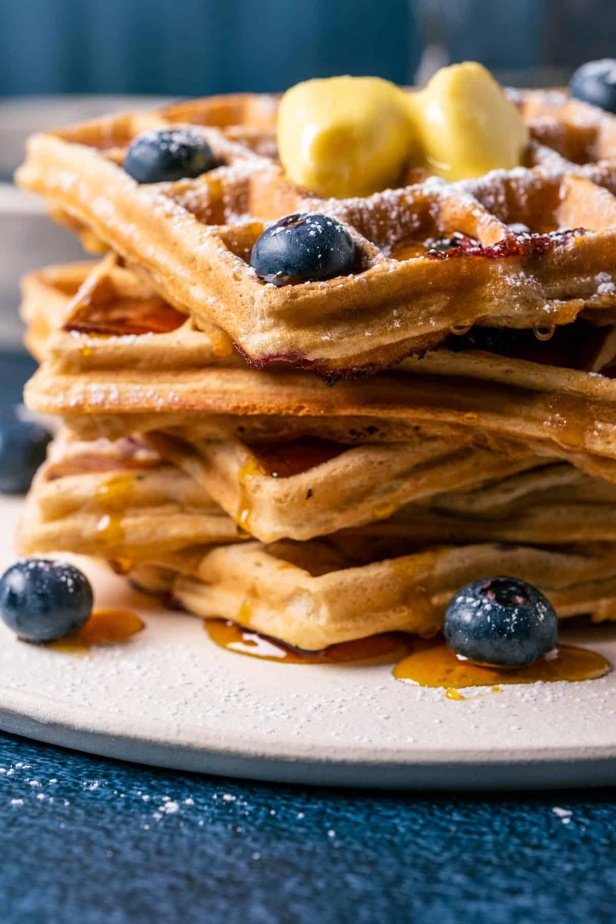 Stack of blueberry waffles topped with vegan butter, powdered sugar and syrup on a white plate.