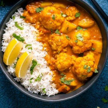 Vegan cauliflower curry with rice and lemon wedges in a black bowl.
