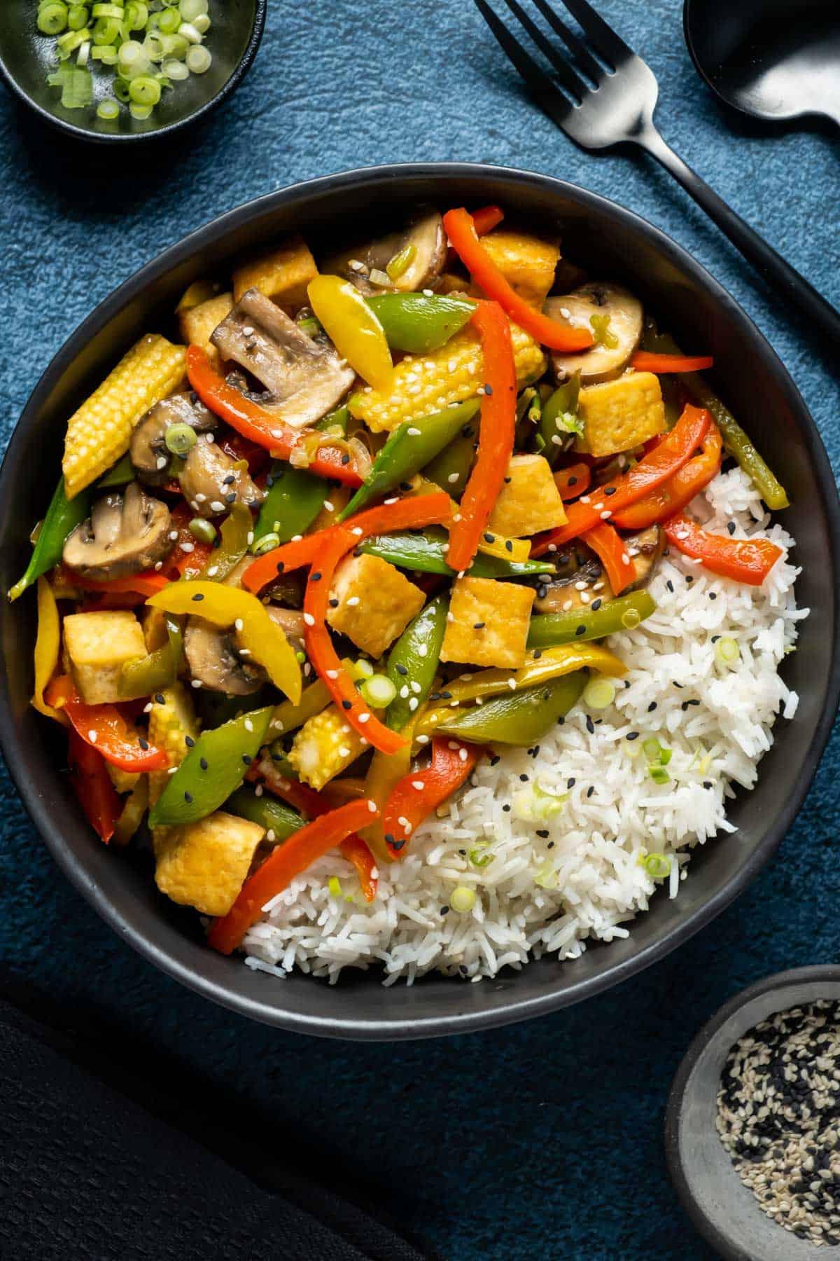 Vegan stir fry with rice in a black bowl.