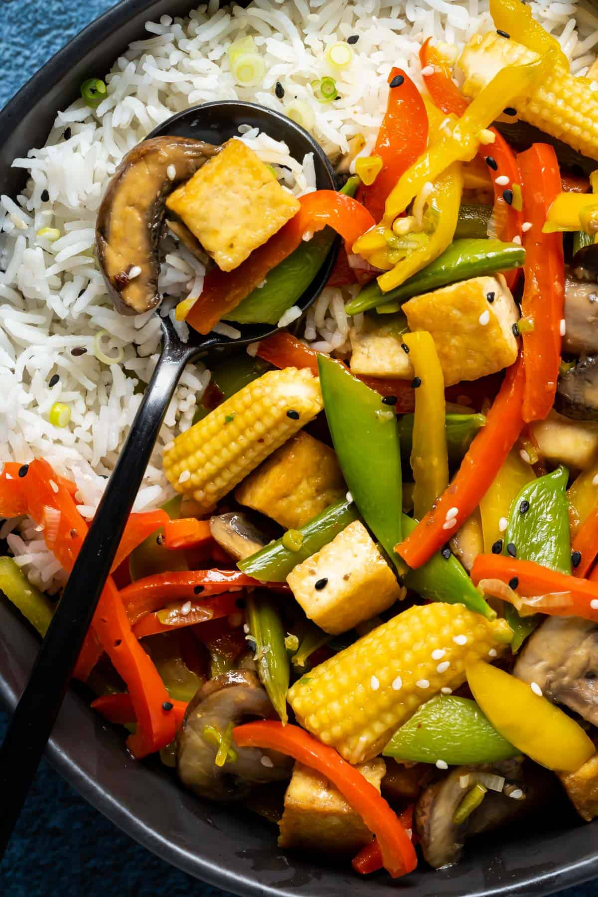 Vegan stir fry and rice in a black bowl with a spoon.
