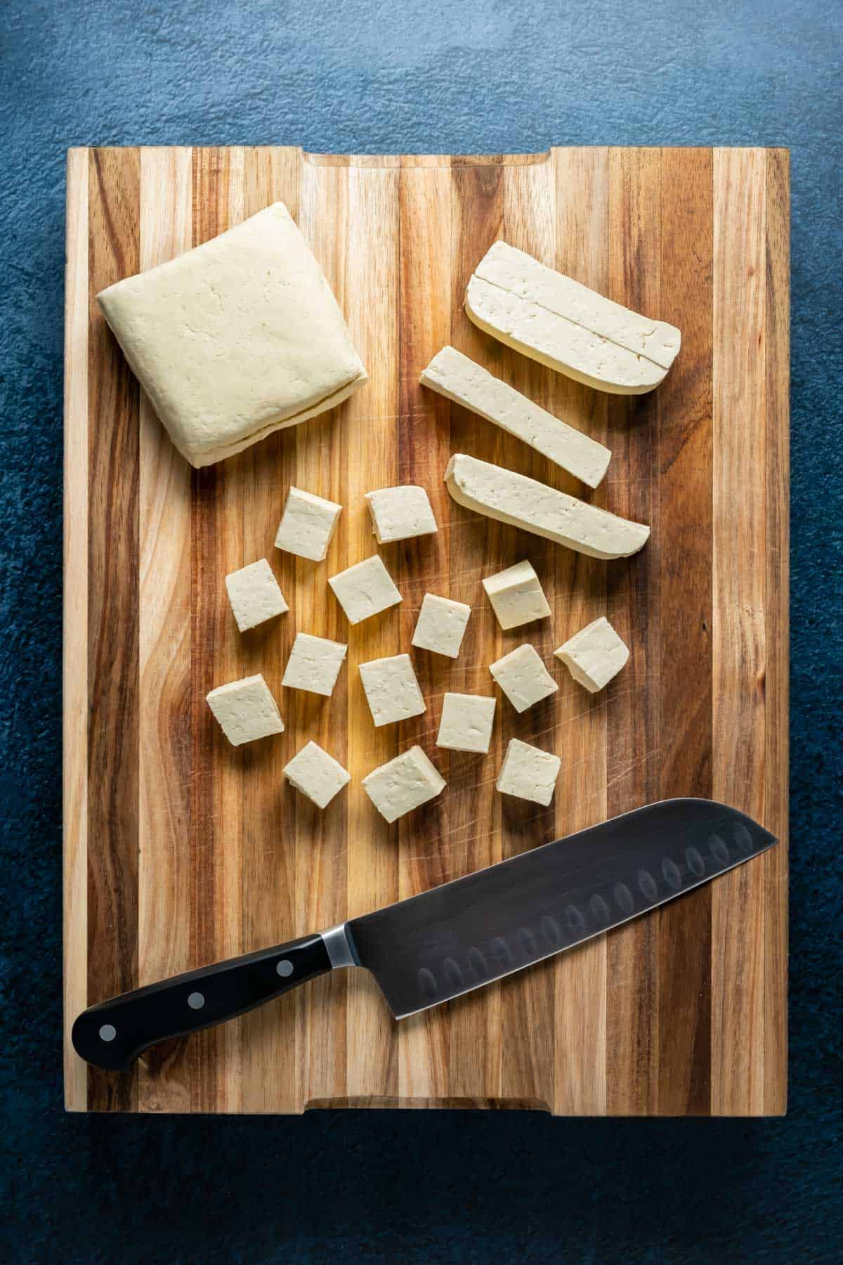 Cutting tofu into cubes on a wooden cutting board.