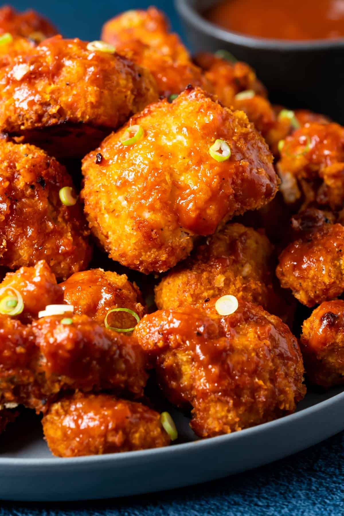 BBQ cauliflower wings on a plate with chopped spring onions.