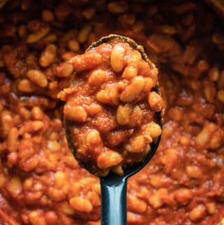 Vegan baked beans in a pot with a serving spoon.