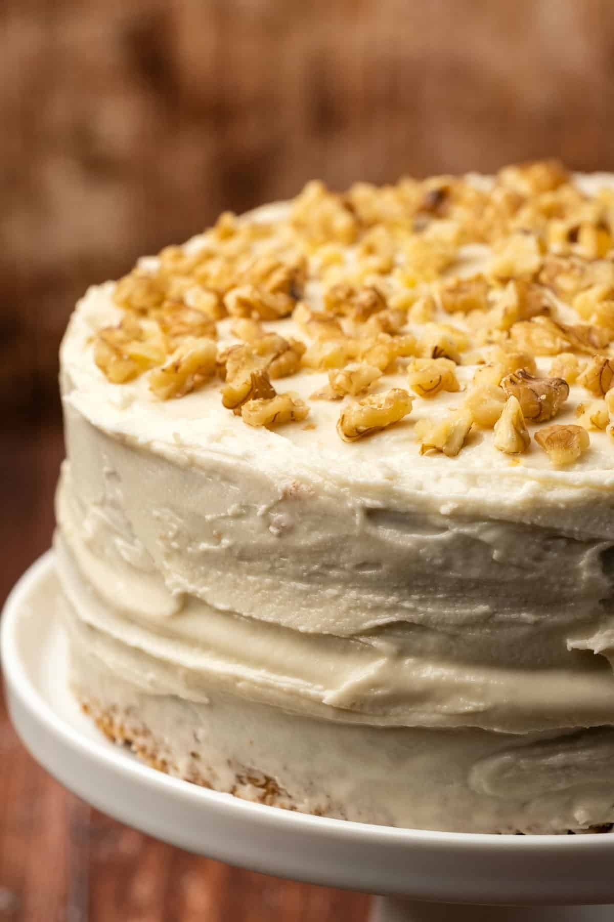 Vegan carrot cake topped with walnuts on a white cake stand.