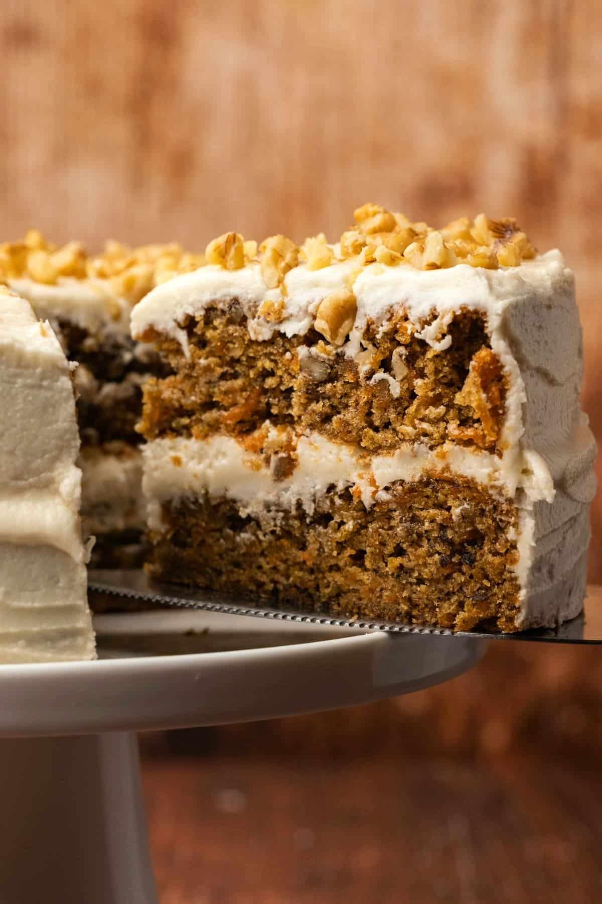 Sliced vegan carrot cake on a white cake stand.