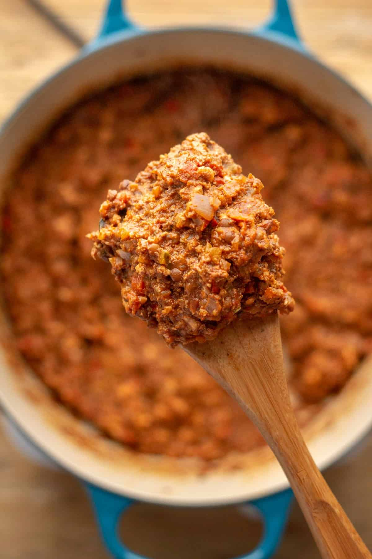 Vegan mince in a pot with a wooden spoon.