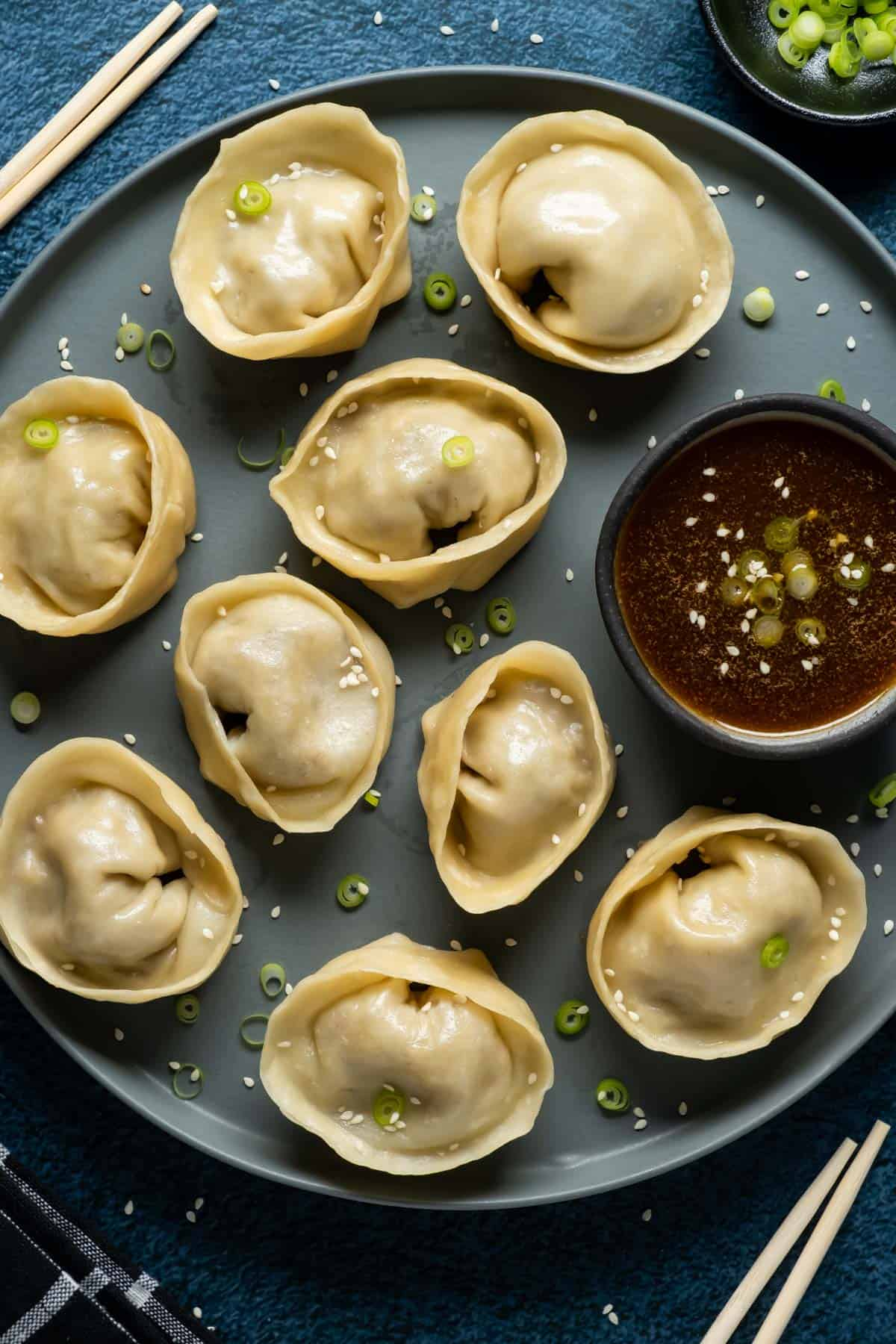 Dumplings topped with chopped green onions on a plate with dipping sauce.