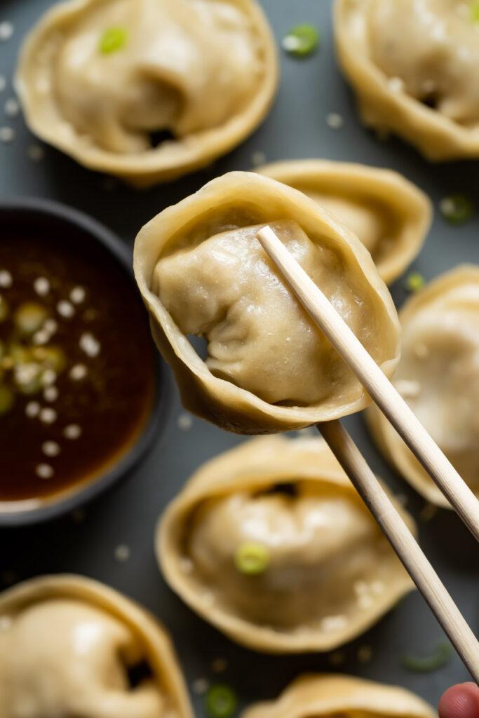 Chopsticks holding a dumpling.