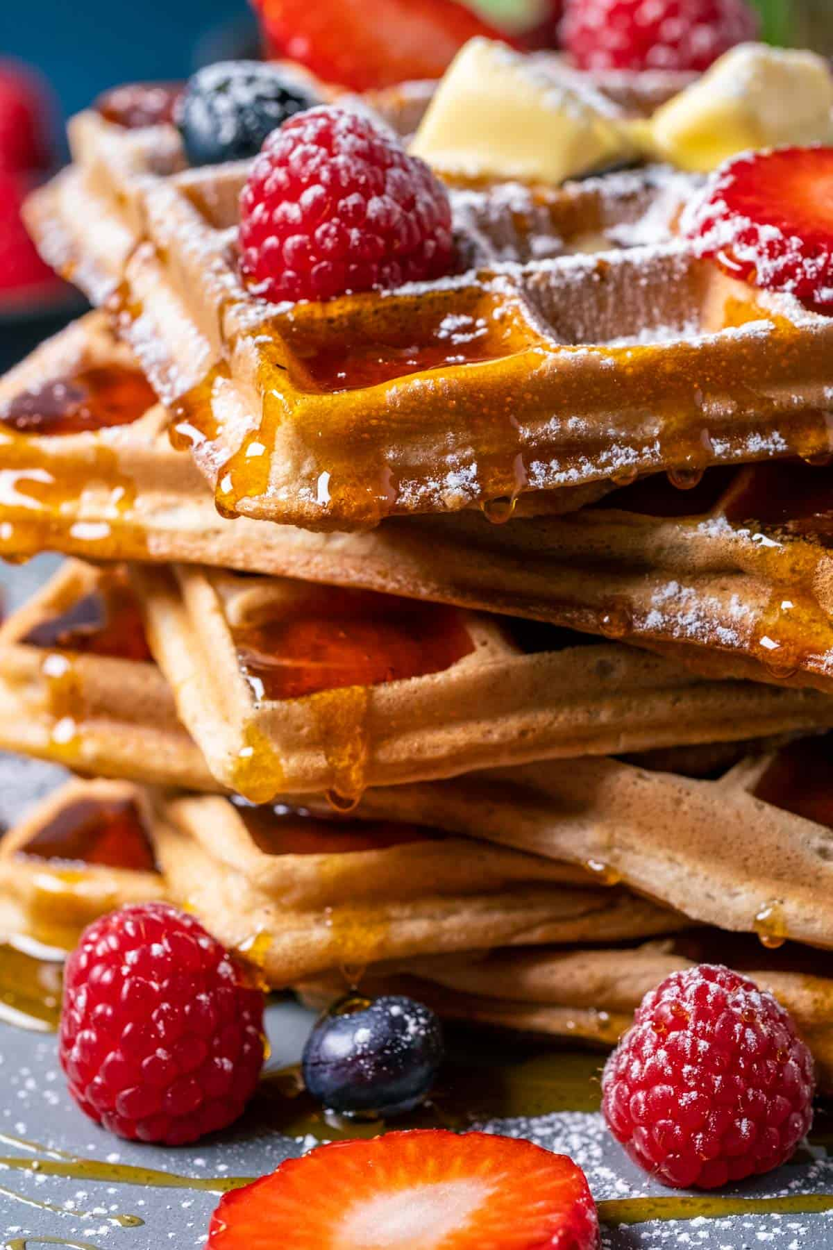 Stack of waffles topped with fresh berries, butter and powdered sugar.