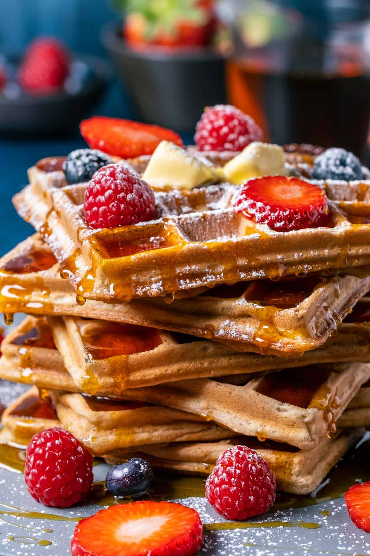 Vegan waffles in a stack topped with vegan butter, powdered sugar and fresh berries.