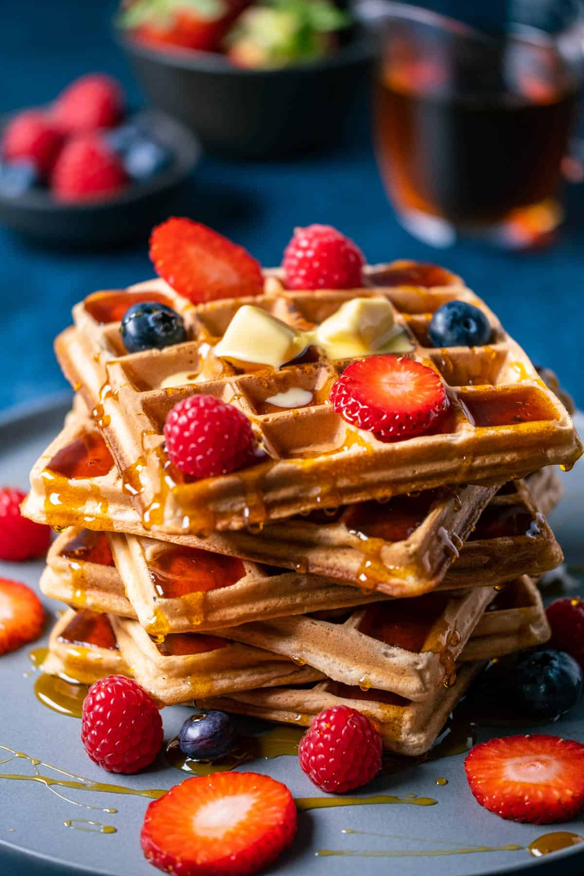 Stack of wafles topped with butter and fresh berries.